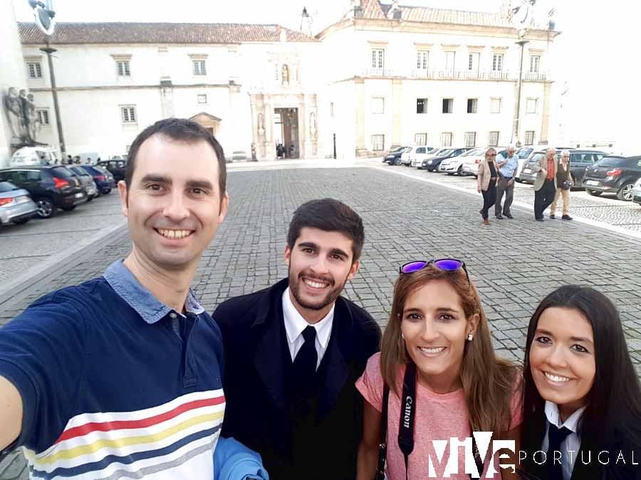 Con dos universitarios con sus capas junto a la entrada de la Universidad de Coímbra
