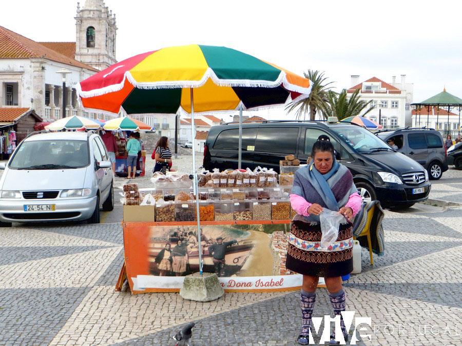 Una vendedora con el traje típico junto a la igreja de Nossa Senhora da Nazaré